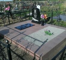 Памятник с розами, подиум с подхоронкой выложен бледно- коричневой плиткиой